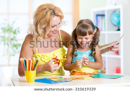 Child with mother cutting out scissors paper in preschool - stock photo