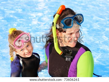 Child with mother in swimming pool learning snorkeling. - stock photo