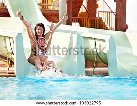 Child with mother on water slide at aquapark. Summer holiday. - stock photo
