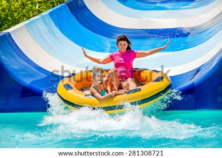 Child with mother on water slide at aquapark. Two persons on summer holiday. - stock photo