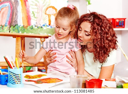 Child with mother painting . Child care.