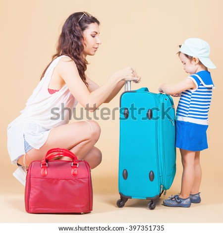 Child with mother ready travel to Europe, Milan. Family carries luggage at white background. Vacation rentals, packages. Airport terminal. Suitcase. Tourism. Tourist bag. - stock photo