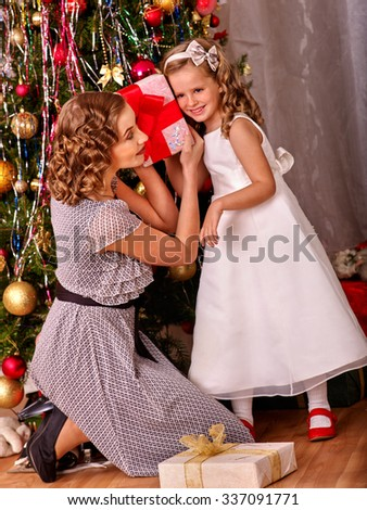 Child with mother receiving and open gifts under Christmas tree. Black and white retro. - stock photo