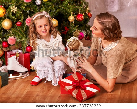 Child with mother receiving  doll gifts under Christmas tree. Vintage style. - stock photo