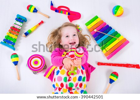 Child with music instruments. Musical education for kids. Colorful wooden art toys for children. Little girl playing music. Kid with xylophone, guitar, flute. Preschooler and toddler early development - stock photo