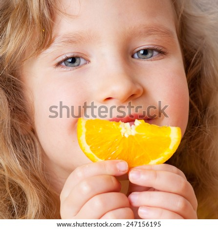 Child with oranges. Happy little girl with fruit at home. - stock photo