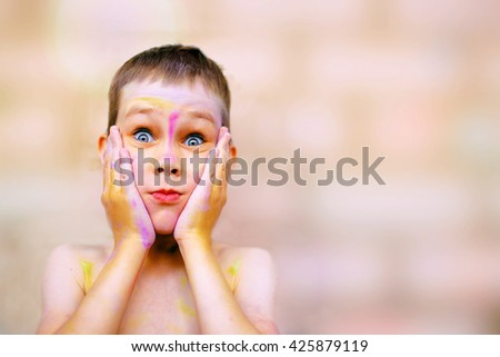 child with painted face very surprised. cute boy with a face stained with paint eyes widened in amazement. copy space for your text - stock photo