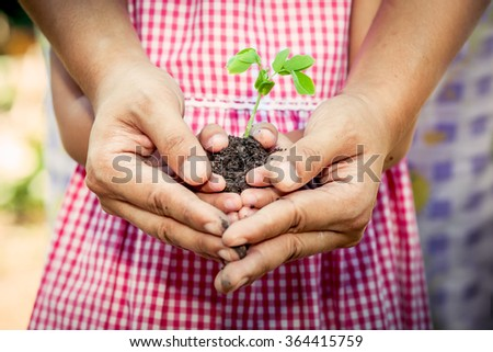 Child with parents hand holding young tree in egg shell together for prepare plant on ground,save world concept,vintage color filter - stock photo