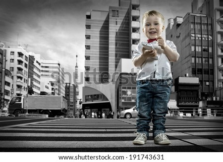 Child with phone stay on the crossroad - stock photo