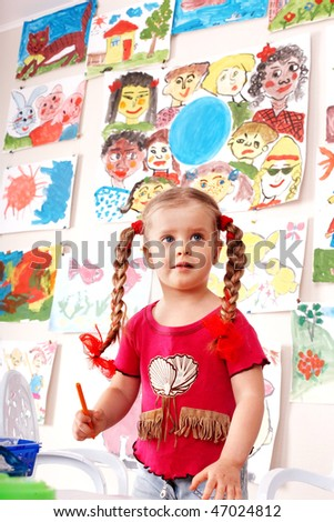Child with picture and brush in playroom. Preschool.