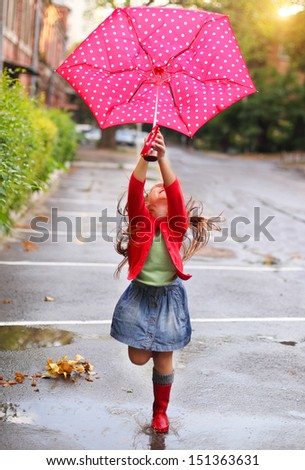 Child with polka dots umbrella wearing red rain boots jumping into a puddle - stock photo