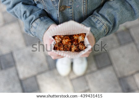 Child with popcorn in hands. Sweet sugar caramelized popcorn pack in little girl's hands, POV composition. Top view of child with popcorn outdoors, sweet snack, street food, fast food. - stock photo