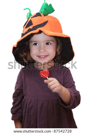 child with pumpkin hat and lollipop - stock photo
