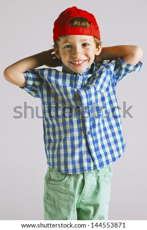 Child with red cap isolated on white./ Portrait of a little boy in studio. - stock photo