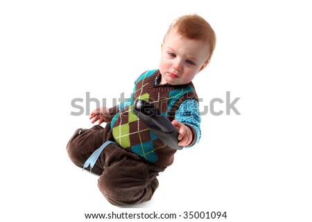 child with remote control isolated on white. toddler with technology in hand and expression of concentration - stock photo