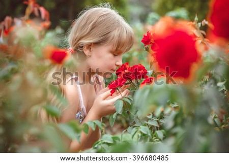 Child with rose flower in spring garden - stock photo