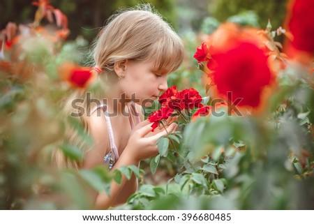 Child with rose flower in spring garden - stock photo