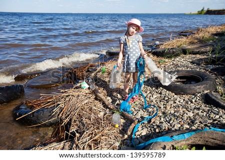 child with rubbish on the bank of river - stock photo