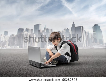 Child with rucksack sitting in front of a laptop with cityscape on the background - stock photo