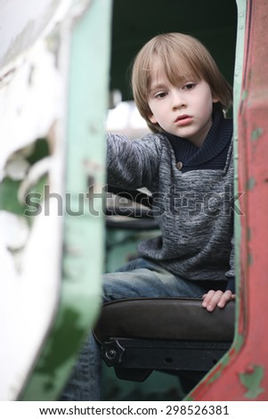 Child with sad facial expression getting out of an old driver cabin - stock photo