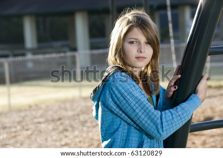 Child with serious expression standing alone on playground (11 years)