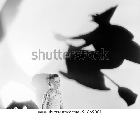 Child with silhouette of witch and jack o lantern