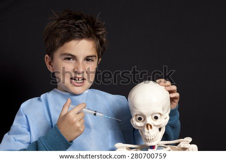 child with skull playing doctor - stock photo
