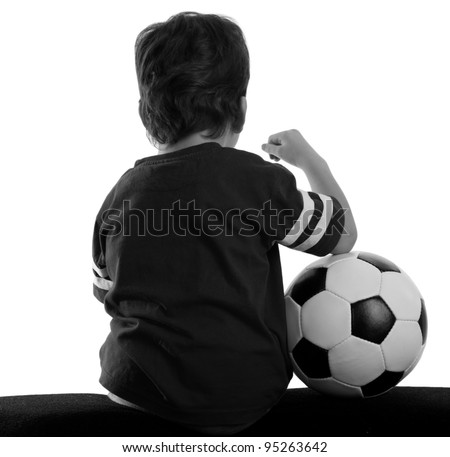 Child with soccer ball sitting back (black white) - stock photo