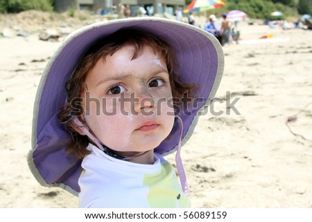 Child with sunscreen and sand on face - stock photo