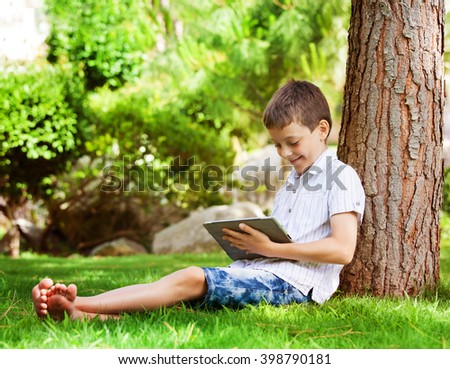 Child with tablet pc outdoors. Boy on grass with computer