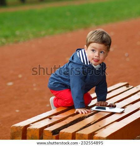 child with the tablet on bench - stock photo