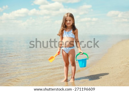 Child with toys and having fun on the beach near sea in summer sunny day - stock photo