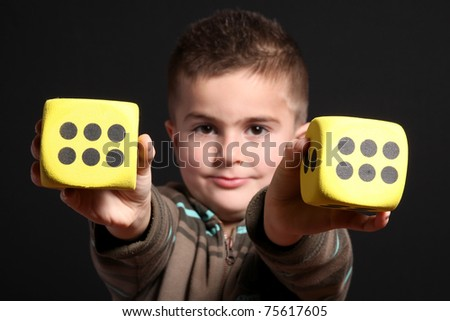child with two yellow dices - stock photo