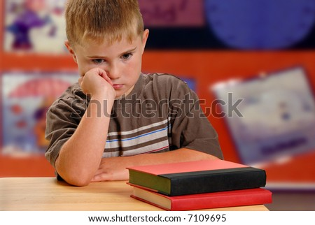 Child with unhappy expression at school desk - stock photo