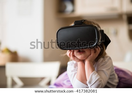 Child with virtual reality headset indoors at home - stock photo