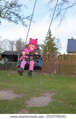 child with warm clothes at the playground on a swing