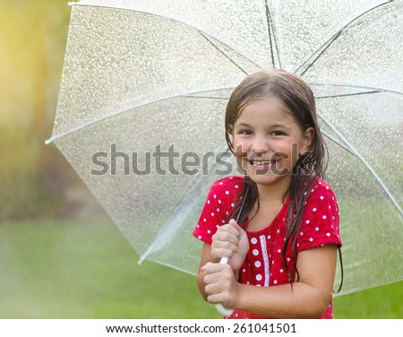 Child with wearing polka dots dress under umbrella in rainy day - stock photo