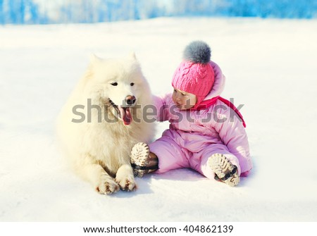 Child with white Samoyed dog sitting on snow in winter day - stock photo