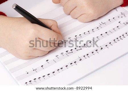 child writing musical notes on school notebook, learning music - stock photo
