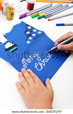 Child writing on christmas greeting card made by hand - stock photo