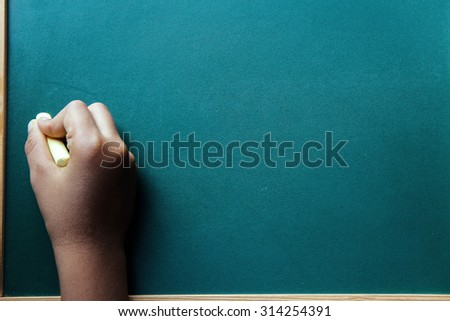 Child writing on wooden board in school. This photo may use as educational background.