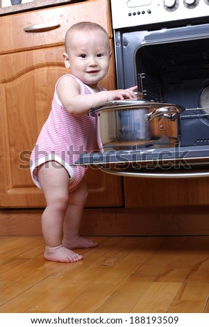 Child 1 year old in the kitchen cooking breakfast
