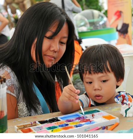 Child 2 years and mother painting in preschool - stock photo