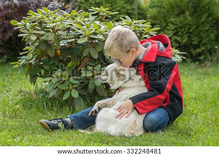 Child young boy lovingly kiss cuddle his pet dog in the garden - stock photo