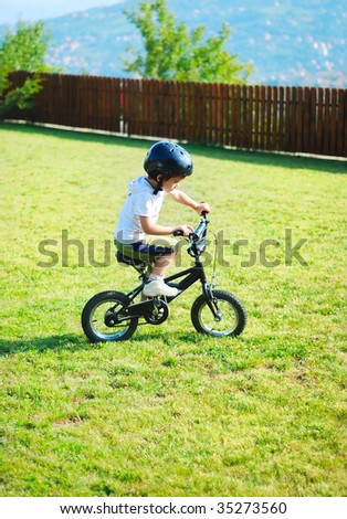Childhood activity with bike on green meadow - stock photo