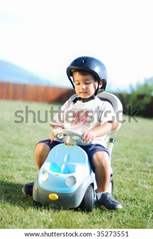 Childhood activity with truck toy on green meadow - stock photo