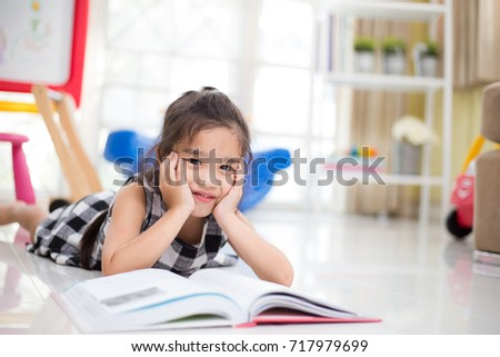 childhood and education concept , Cute  asian girl  reading a book  while  in the live room.