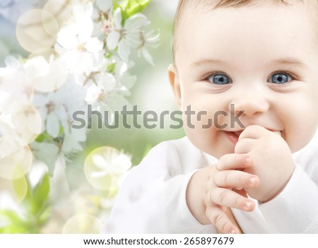 childhood, babyhood, summer, spring and health concept - closeup of happy baby boy or girl over green blooming garden background - stock photo