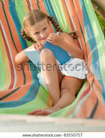 Childhood - Cute girl reading a book in colorful hammock - stock photo