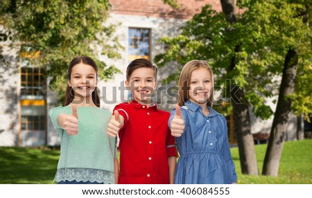 childhood, education, holidays, gesture and people concept - happy smiling boy and girls showing thumbs up over campus and summer park background - stock photo